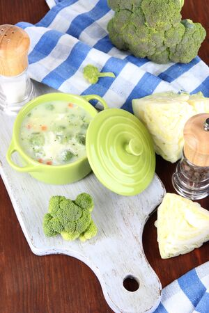 Cabbage soup in plate on board for cutting near napkin on wooden table photo