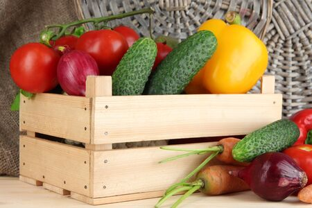 Fresh vegetables in box on wooden table close up photo