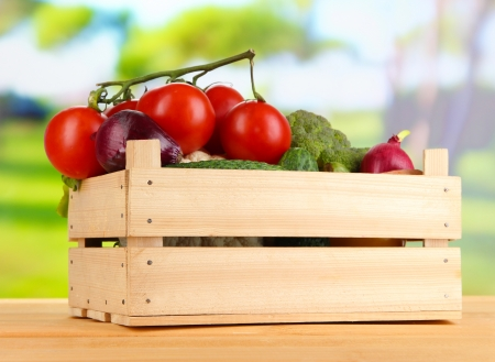 Fresh vegetables in wooden box on bright background photo