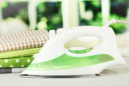Steam iron on bright background photo