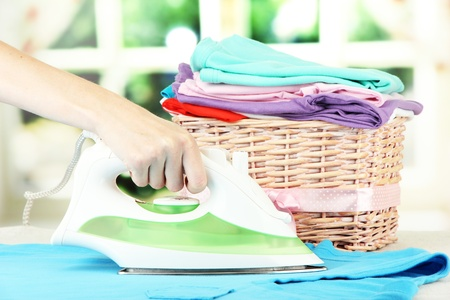 ironing: Womans hand ironing clothes, on bright background