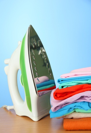 Steam iron with clothes, on color background photo