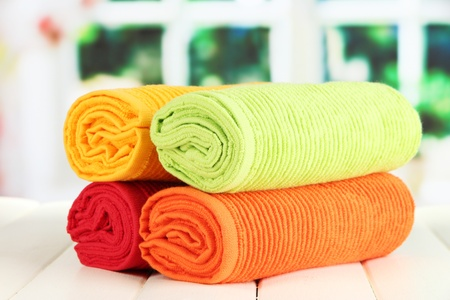 Colorful towels on wooden table on window background Stock Photo - 20967050