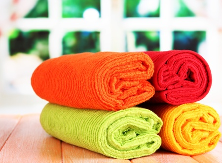 Colorful towels on wooden table on window background Stock Photo - 20966974