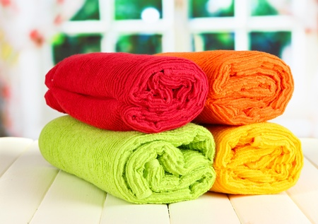 Colorful towels on wooden table on window background Stock Photo - 20966976