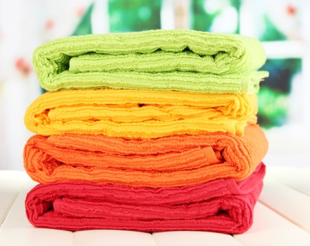 Colorful towels on wooden table on window background Stock Photo - 20967117
