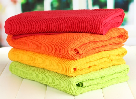 Colorful towels on wooden table on window background photo