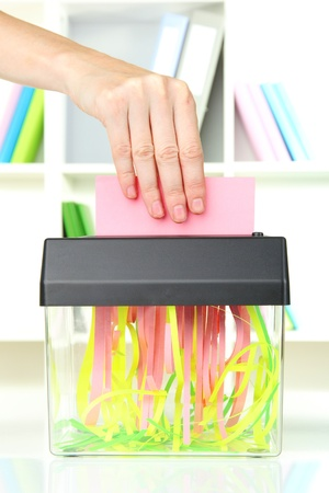 shredder machine: Hand putting paper into shredder machine, on office interior background