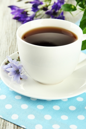 Cup of tea with chicory, on wooden table photo