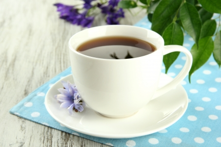 chicory coffee: Cup of tea with chicory, on wooden table