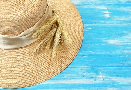 spikelets: Beautiful summer hat with spikelets on blue wooden background