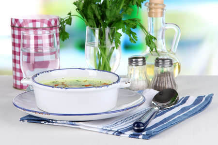 Soup in plate on napkin on table on window background photo