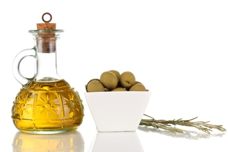 Green olives in white bowl with rosemary and olive oil isolated on white photo