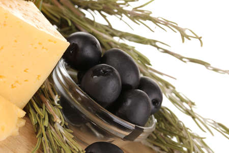 Black olives in white bowl with rosemary,olive oil and cheese on board close-up isolated on white photo