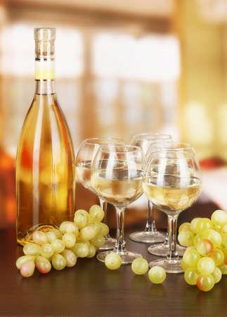 degustation: White wine in glass and bottle on room background
