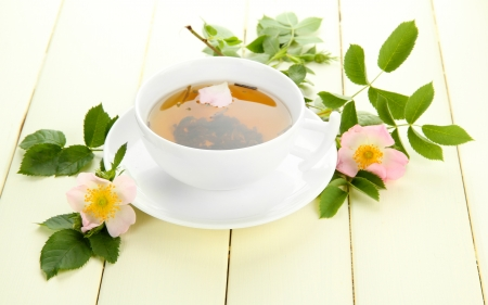Cup of herbal tea with hip rose flowers on white wooden table photo