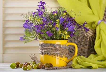 Beautiful bouquet of wildflowers in cup and berries on wooden table photo