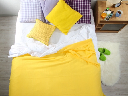 view of a comfortable bedroom: Medicines on nightstand near bed in room close-up