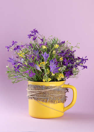 Beautiful bouquet of wildflowers in cup on purple background photo