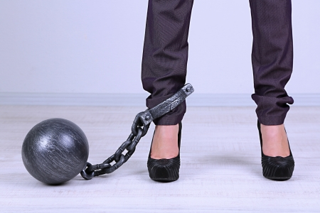 restraining: Business worker with ball and chain attached to foot Stock Photo