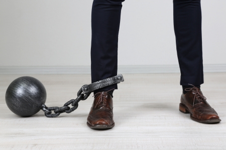 enslave: Business worker with ball and chain attached to foot Stock Photo