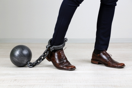 ball and chain: Business worker with ball and chain attached to foot Stock Photo