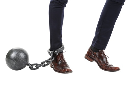 office slave: Business worker with ball and chain attached to foot isolated on white