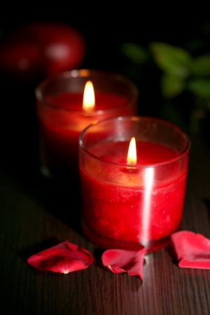Beautiful romantic red candles with flower petals on dark wooden background photo