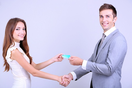 Business partners changing business cards on grey background photo