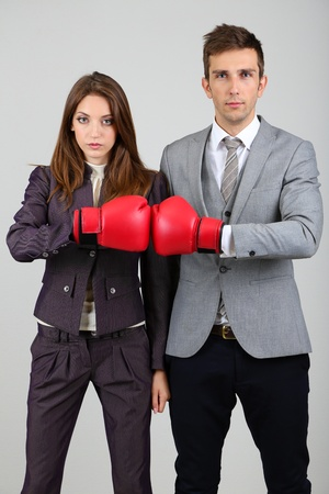 Young business people in boxing gloves on grey background photo