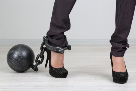 heavy: Business worker with ball and chain attached to foot Stock Photo