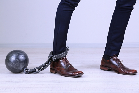 Business worker with ball and chain attached to foot Stock Photo