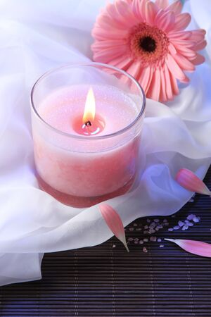 Beautiful pink candle with flower on bamboo mat photo