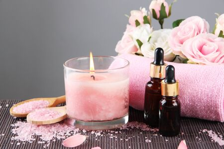 Beautiful pink candle with flowers and towel on bamboo mat photo