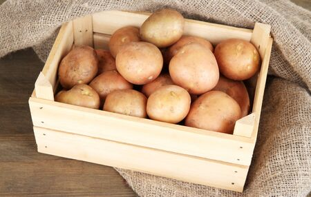 Potato on wooden table photo