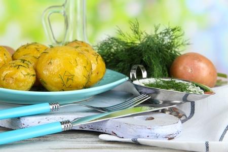 platen: Boiled potatoes on platen on wooden board near napkin on wooden table on nature background Stock Photo