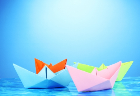 Paper ships of different colors on water background photo