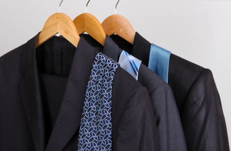 Suits and ties on hangers on gray background photo