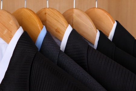 clothing rack: Suits with shirts on hangers on wooden background