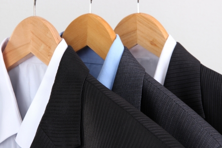 Suits with shirts on hangers on light background photo