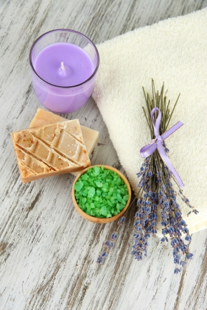 Still life with lavender candle, soap,   soap and fresh lavender, on wooden background photo
