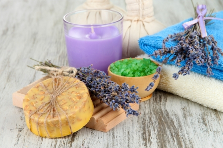 Still life with lavender candle, soap, massage balls, bottles,  soap and fresh lavender, on wooden background photo