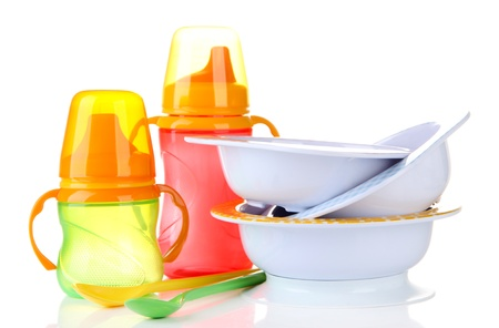 baby cutlery: Biberones brillantes, tazones y cucharas aislados en blanco
