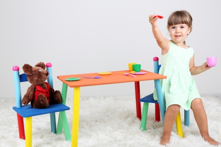 Little cute girl sitting on little chair near table, on gray background photo