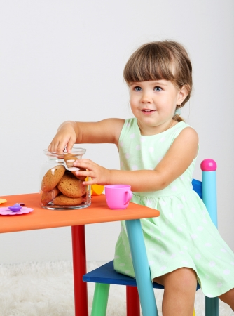Little cute girl sitting on little chair near table and eating tasty cookie, on gray background photo