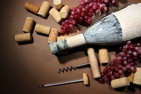 Old bottle of wine, grapes and corks on brown background photo