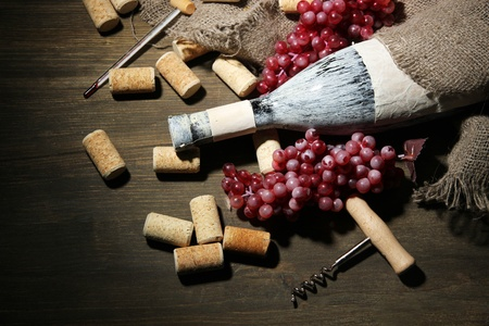 Old bottle of wine, grapes and corks on wooden background photo