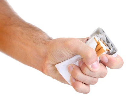 Fist with crushed pack of cigarettes, isolated on white photo
