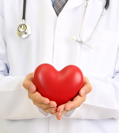 Medical doctor holding heart  isolated on white photo