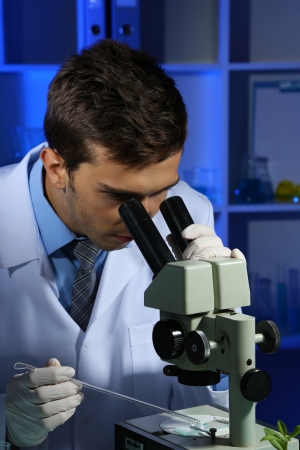 Young laboratory scientist looking at microscope in lab photo